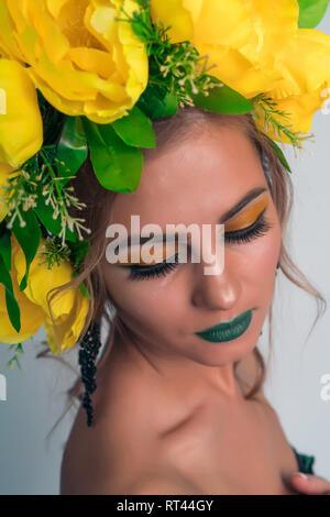 Close-up volto di una bellissima ragazza con brillante trucco e grandi fiori gialli sul suo capo Immagini Stock