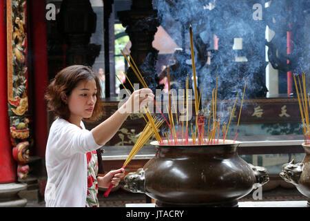 Adoratore buddista immissione bastoncini di incenso su joss stick pot, Tempio Taoista, Phuoc un Hoi Quan Pagoda, Ho Chi Minh City, Vietnam, Indocina, sud-est Immagini Stock