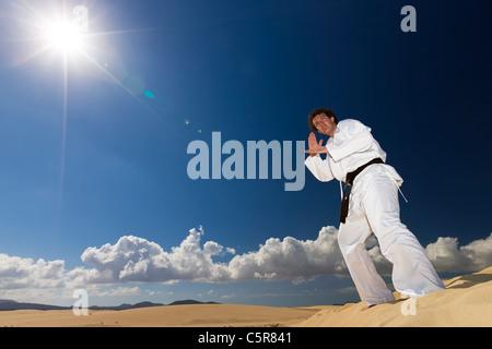 La cintura nera di arti marziali formazione sulle dune del deserto. Immagini Stock