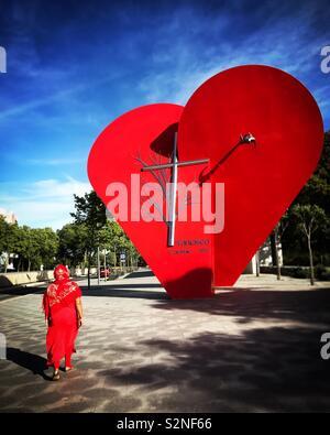 Un turista vestito di rosso in visita a un monumento con un cuore rosso e una croce a Fatima, Portogallo Immagini Stock