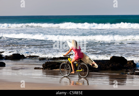 Una bionda surfer girl passeggiate lungo la spiaggia per le onde. Immagini Stock