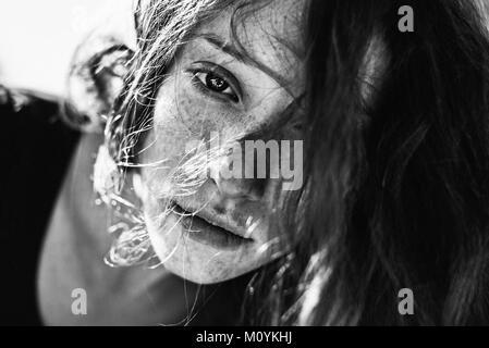 Capelli che ricopre la faccia della donna caucasica Immagini Stock