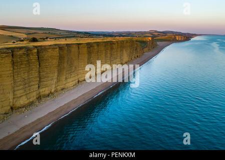 Immagine drone di caldo della spiaggia e scogliere in West Bay Dorset durante il crepuscolo. Immagini Stock