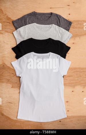Pila di colore diverso womens T-shirt su sfondo di legno. Vedi verticale. Immagini Stock