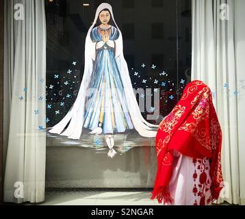 Un messicano indossando un velo guarda un dipinto della Madonna del Rosario di Fatima, Portogallo Immagini Stock