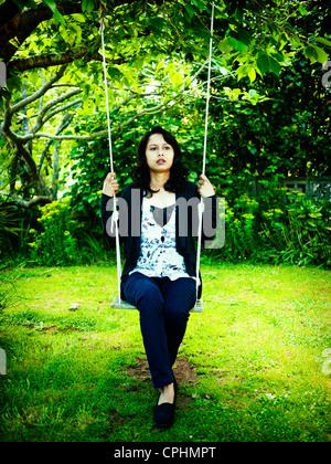 Punjabi donna su altalena in giardino Immagini Stock