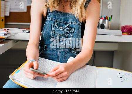 Femmina giovane studente di college prendendo una pausa dallo studio, sms con smart phone Immagini Stock