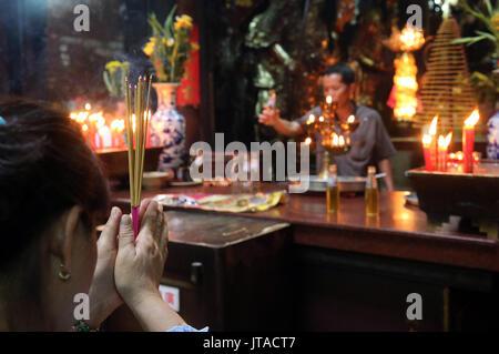 Adoratore buddista bruciare bastoncini di incenso, Tempio Taoista, pagoda dell'Imperatore di Giada (Chua Phuoc Hai), la città di Ho Chi Minh, Vietnam, Indocina, sud-est asiatico, Immagini Stock