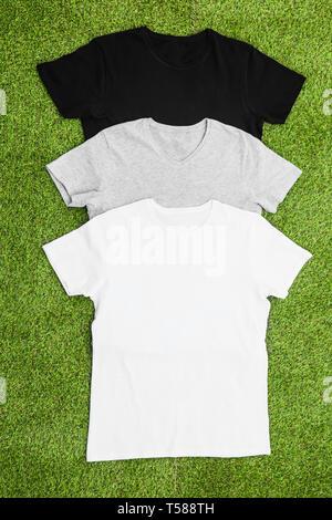 Pila di colore diverso mens T-shirt su sfondo di erba. Vedi verticale. Immagini Stock