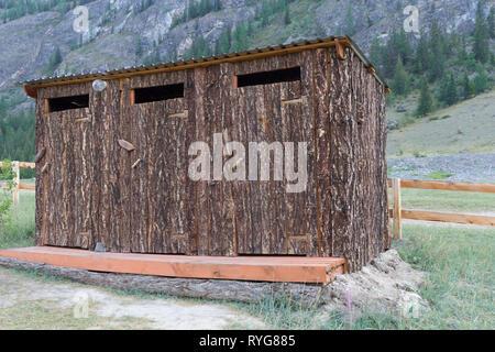 Toilette in legno all'esterno in una zona montagnosa Immagini Stock