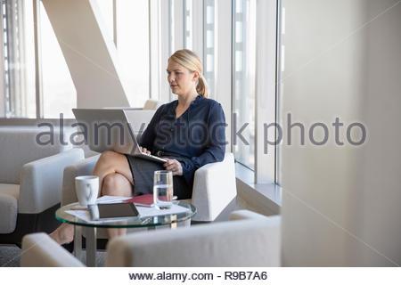 Imprenditrice utilizzando computer portatile in ufficio lounge Immagini Stock