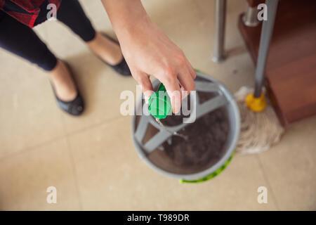 La donna è il pavimento di versamento di liquido di lavaggio dal dado alla benna e mop è in piedi vicino a. Immagini Stock