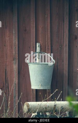 Il vecchio secchio appeso alla parete di edificio rurale. Vintage attrezzature agricole. Immagini Stock