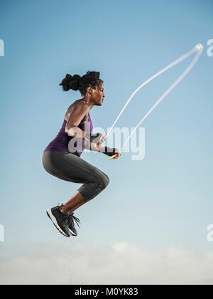 Nero donna salto con la corda nel cielo Immagini Stock
