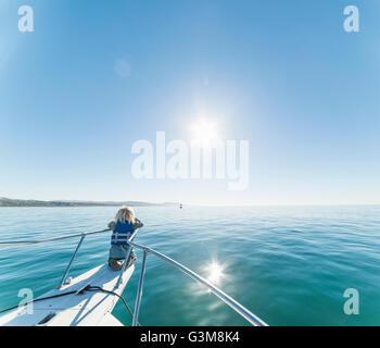 Ragazzo inginocchiato a bordo di navi di prua di una barca a vela che guarda lontano Immagini Stock