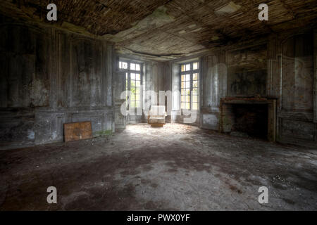 Vista interna di una camera con sedia in un angolo dalla finestra di un castello abbandonato in Francia. Immagini Stock