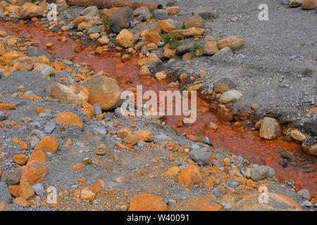 Un uomo locale cosparsi di acqua primavera con alto contenuto di Ferrum che dà un arrugginito di colore arancione al dzhily su molla nella Repubblica Kabardino-Balkar nel Nord Caucaso Distretto federale della Russia. Immagini Stock