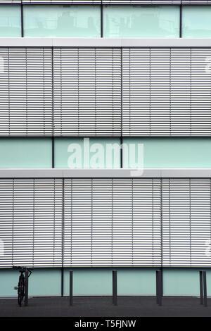 La facciata di un edificio moderno con una bici di fronte ad esso. Immagini Stock