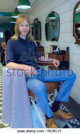 Ritratto di un barbiere in seduta barbiere sedia Immagini Stock