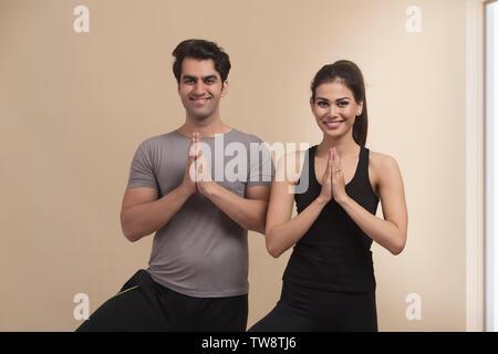 Coppia giovane in piedi in posizione di yoga Immagini Stock