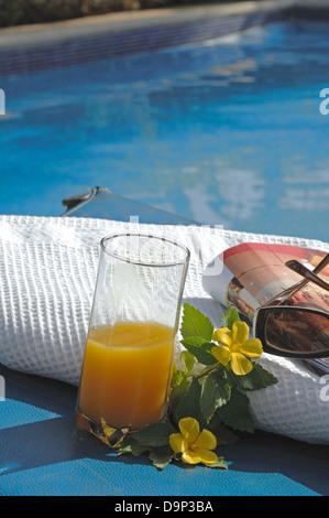 Bicchiere di succo di arancia a bordo piscina Immagini Stock