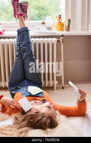 Femmina giovane studente universitario che studia con le schede flash sul pavimento Immagini Stock