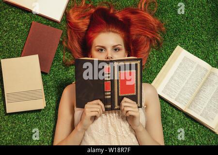 I Capelli rossi ragazza distesa su erba e guarda da dietro il libro Immagini Stock