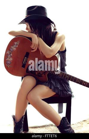 Bruna seduta, in appoggio alla chitarra Immagini Stock