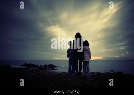 Madre del figlio e figlia, oceano tramonto, Nuova Zelanda. Immagini Stock