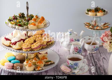High Tea, o il tè del pomeriggio steso su una tabella con i tradizionali tazze e piattini. Immagini Stock
