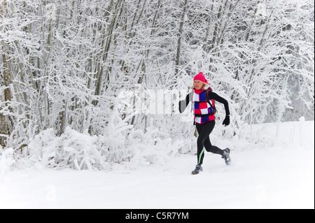 Jogging attraverso una coperta di neve foresta. Immagini Stock