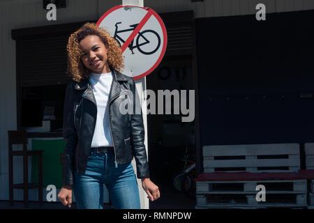 Bella ragazza africana sorridente ponendo in piedi vicino al parcheggio per biciclette Immagini Stock