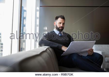 Architetto maschio rivedendo blueprint sul divano per ufficio Immagini Stock