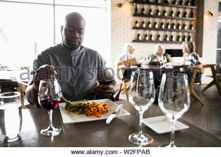 Uomo con smart phone a pranzo nel ristorante Immagini Stock