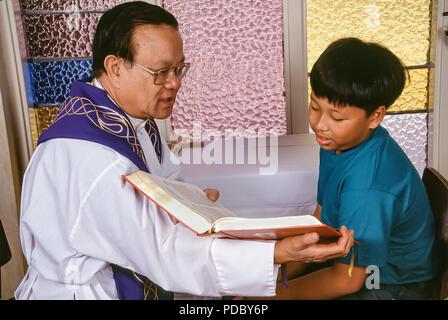 Ragazzo giovane leggendo la Bibbia al sacerdote durante la riconciliazione. © Myrleen Pearson ....Ferguson Cate Immagini Stock