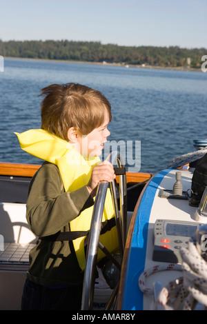 Un ragazzo lo sterzo una barca Immagini Stock