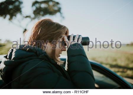 Colpo alla testa di una donna con il binocolo in una giornata di sole Immagini Stock