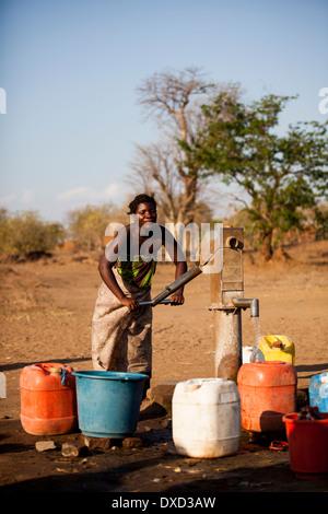 Africa donna il pompaggio di acqua in un tubo di supporto Immagini Stock