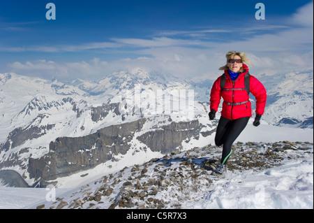 Donna jogging su alte vette innevate. Immagini Stock