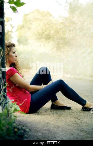 Casual giovane donna seduta in posizione di parcheggio Immagini Stock