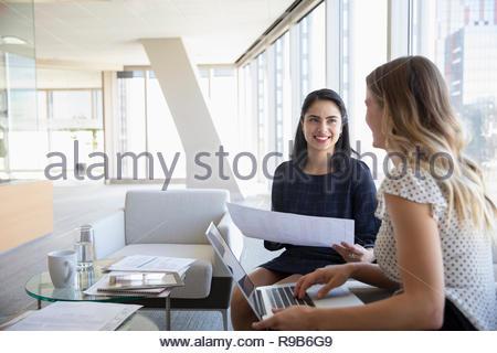 Imprenditrici con la documentazione e il computer portatile in ufficio Immagini Stock