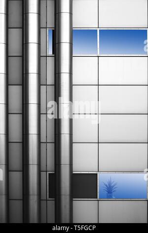 La fotografia astratta ed installazione di tubazioni in acciaio inox a un metallo di foglio di facciata con un vaso di fiori. Immagini Stock
