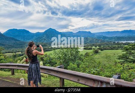 Hanalei Kauai Hawaii donna prendendo video affacciato sulla Baia di Hanalei dal di sopra Immagini Stock