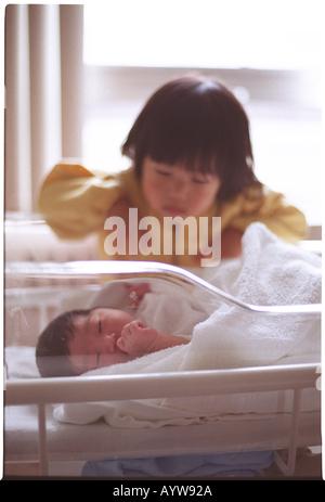 Ragazza cerca in un neonato Immagini Stock