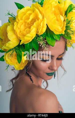 Moda ritratto di una bella ragazza bionda con una ghirlanda di grandi fiori gialli sul suo capo e brillante trucco su sfondo grigio Immagini Stock