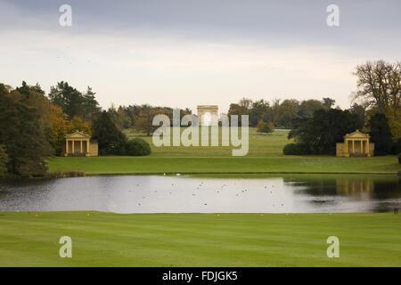 Vista sul lago di Ottagono verso il lago di padiglioni e Corinthian Arch a Stowe giardini paesaggistici, Buckinghamshire. Immagini Stock
