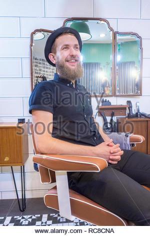 Ritratto di un barbiere udienza del barbiere's chair, rilassante Immagini Stock