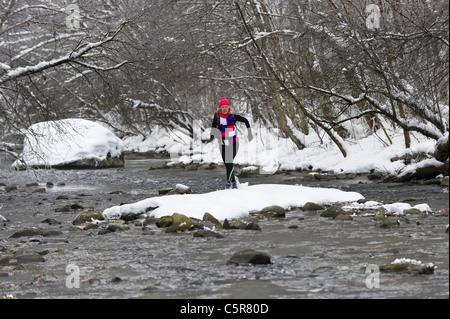 Un pareggiatore attraversando un freddo fiume alpino. Immagini Stock