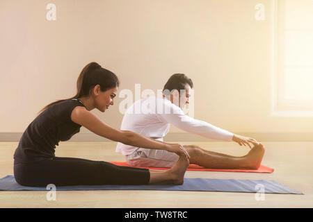 Coppia giovane facendo stretching esercizio sul materassino yoga Immagini Stock
