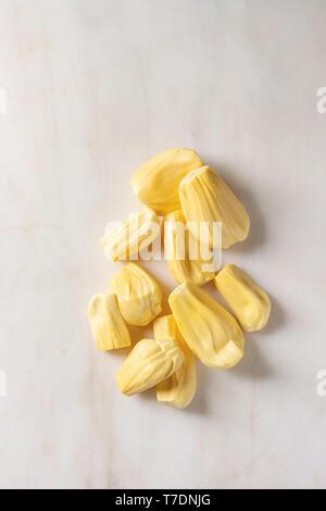 Raw maturo pelato jackfruit su marmo bianco dello sfondo. Laici piana, spazio Immagini Stock